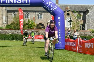 Sam James crossing the finishing line for British Heart Foundation 50 mile cycle ride